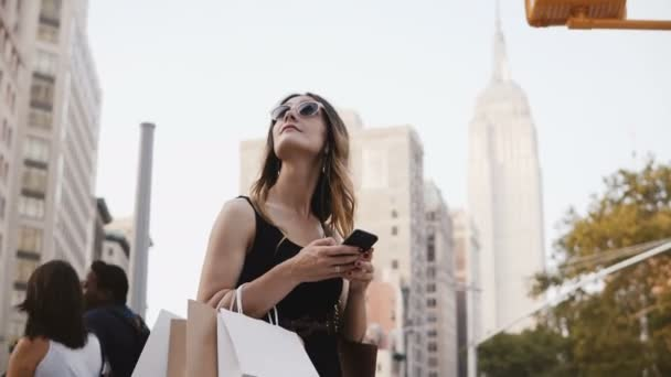 Happy attractive Caucasian young woman with shopping bags in sunglasses looking up, using smartphone app in New York.