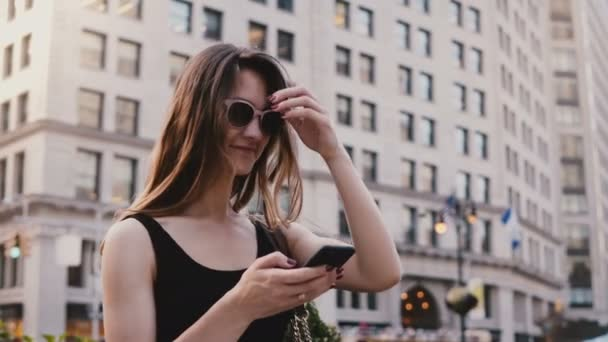 Amazing panning shot of excited Caucasian young tourist woman with smartphone in sunglasses looking around in New York.