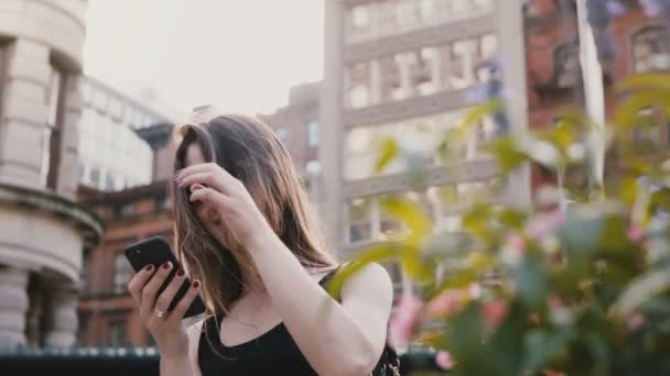 Happy excited Caucasian female blogger in sunglasses using smartphone shopping app, touching hair in summer New York.