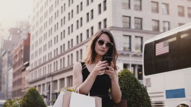 Happy attractive Caucasian businesswoman with shopping bags chatting with friends on smartphone social app in New York.
