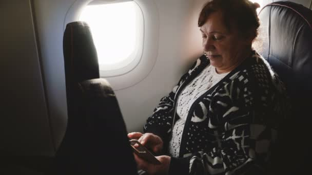 Serious senior airplane passenger woman typing messages on smartphone messenger app sitting on airplane window seat.