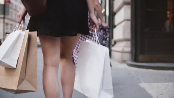 Zadní pohled na úspěšné mladé dívky závislý na nákupní odnosné tašky v obou rukou, chůze po ulici Zpomalený pohyb