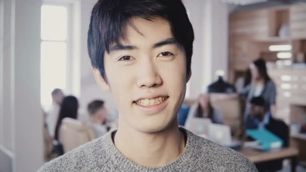 Close-up portrait of successful Asian male creative manager smiling at modern office. Handsome man looking at camera 4K.
