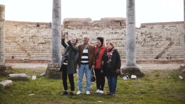Smiling young European girl and happy senior tourist group taking selfie near old amphitheater ruins in Ostia, Italy.