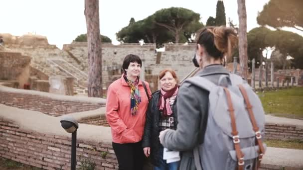 Young beautiful European girl taking a photo of two senior women near old historic ruins in Ostia, Italy on vacation.