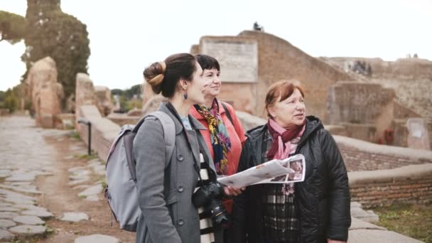 Young Caucasian female excursion tour guide giving detail on historic ruins of Ostia, Italy to two senior women tourists