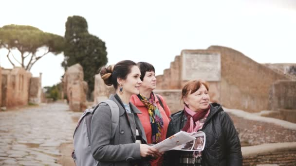 Two Caucasian senior female travelers and young woman guide enjoy exploring historic ruins of Ostia, Italy on vacation.