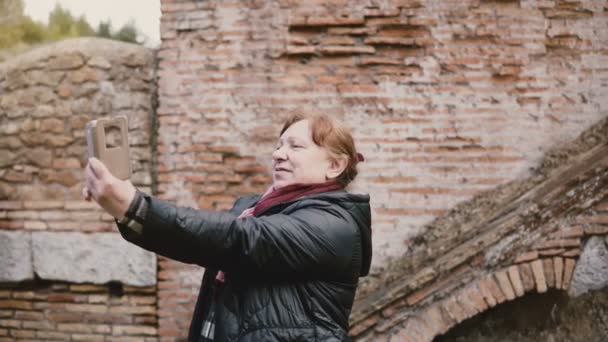 Excited happy senior Caucasian tourist woman taking selfie using smartphone at historic ancient ruins in Ostia, Italy.