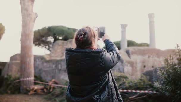 Excited happy senior smiling European woman taking phone photo of ancient pillar ruins in Ostia, Italy on vacation trip.