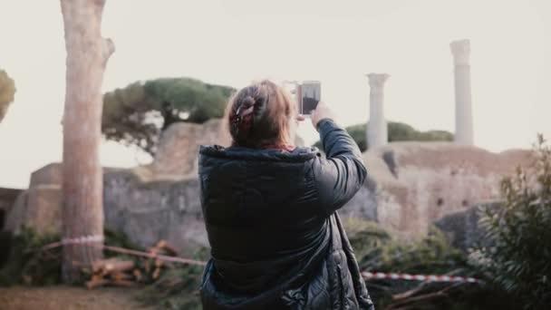 Izgatott boldog vezető mosolygó európai nő telefon fénykép pillér ősi romok, Ostia, Olaszország nyaralás utazás.
