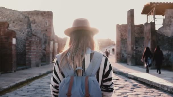 Back view of girl in hat with backpack standing in the middle of ancient antique street in Pompeii, Italy on a sunny day