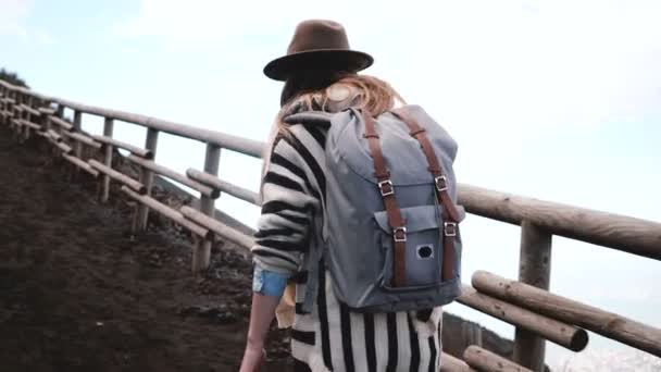 Back view of young stylish tourist woman with backpack hiking alone to the top of Vesuvius volcano in Italy on vacation.