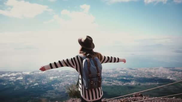 Back view happy female travel blogger with flying hair coming up to epic mountain top scenery on Vesuvius arms wide open
