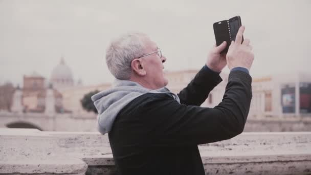 Happy excited senior male tourist taking a photo of ancient city buildings in Rome, Italy using smartphone slow motion.