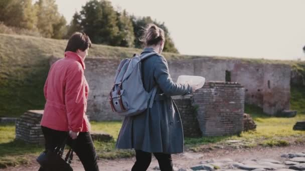 Side view of European mother and daughter with a map walking together along historic old town of Ostia slow motion.