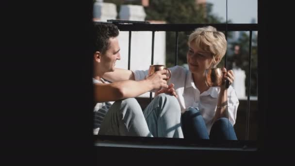 Beautiful young multiethnic man and woman sitting together at a small sunny balcony with bronze metallic mugs and smile.
