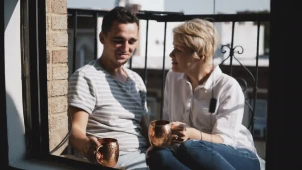 Beautiful young multiethnic couple having coffee at small sunny balcony with bronze metallic mugs, talk and smile.