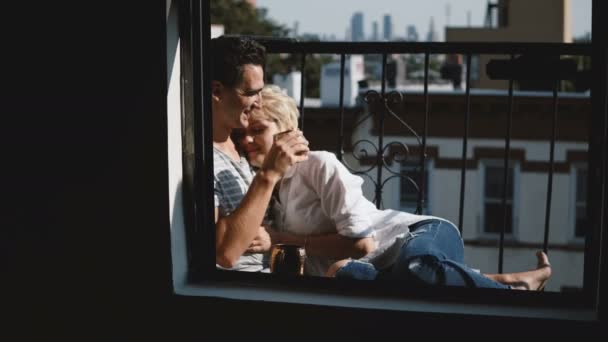 Beautiful multiethnic romantic couple sitting close together and talking at lovely balcony, woman leaning head to man.