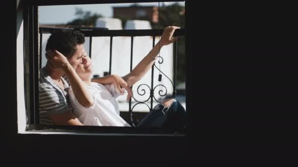 Happy man and woman sitting close together at beautiful romantic sunny apartment balcony, talking about future plans.