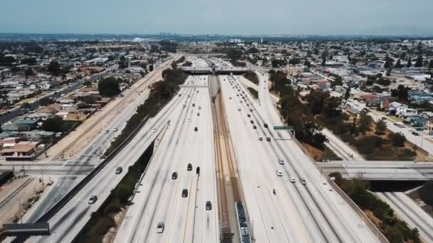 Amazing cinematic aerial shot of busy American interstate highway with heavy car traffic moving on multiple levels.