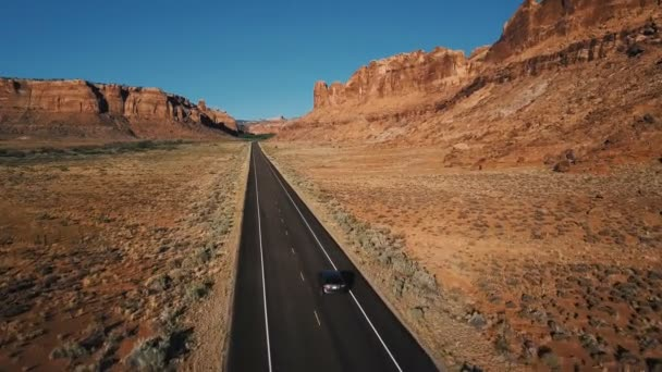 Drone camera follows silver car moving along straight desert highway road among amazing rocky mountain landscape in USA.