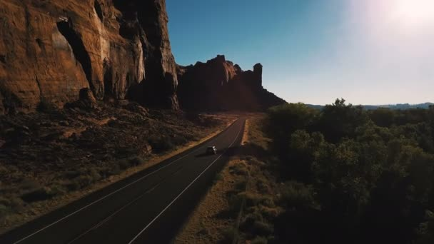 Drone camera follows car driving along small desert highway road near breathtaking steep canyon ridge on sunset in USA.