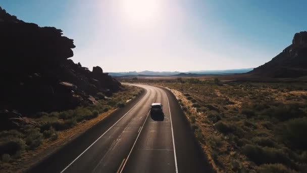 Drone camera follows minivan car turning left on desert highway road between breathtaking open spaces and mountains.