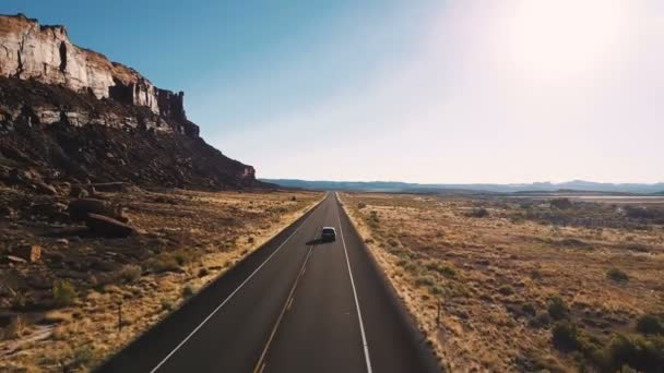 Drone follows car driving along highway road between epic steep canyon mountain ridge and amazing desert skyline in USA.