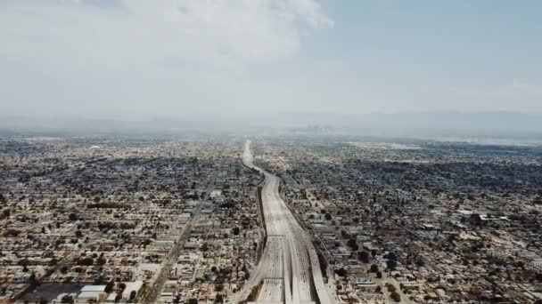 Epic panoramic aerial view of amazing American suburbs skyline, beautiful blue sky and large highway busy with traffic.