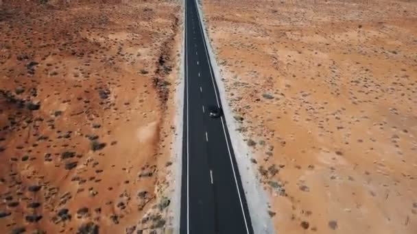 Drone following and zooming in on silver car driving along sunny American desert landscape on empty highway road.