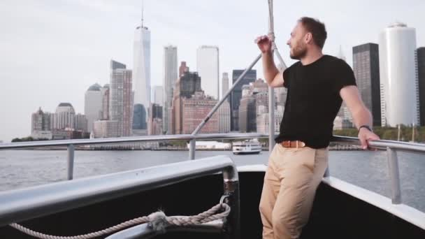 Happy excited tourist man smiling, enjoying Manhattan Island skyline view in New York from a tour boat slow motion.