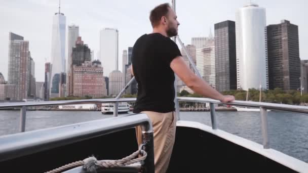 Happy thoughtful successful businessman enjoying Manhattan Island cityscape skyline view from a yacht front slow motion.