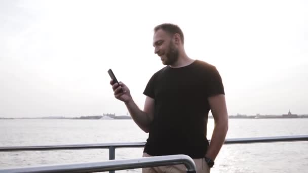 Happy successful Caucasian entrepreneur using smartphone, looking around on a beautiful sunset boat trip slow motion.