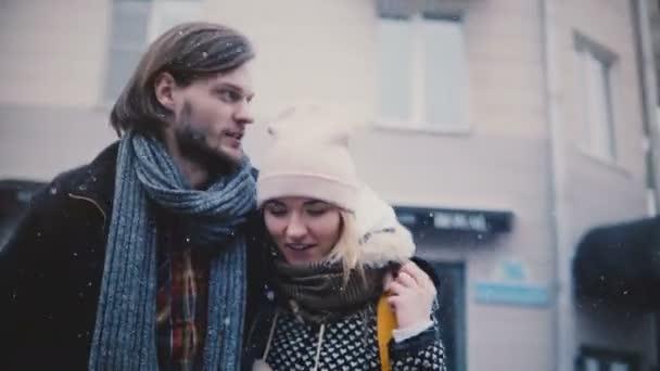 Šťastný uvolněný mladý romantický pár v teplé oblečení blízko sebe chodí, mluví a úsměv na velmi studené zasněžené zimní den