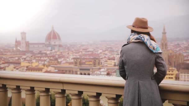 Back view of girl in hat standing at observation deck enjoying amazing view of Florence, Italy on cold rainy cloudy day.