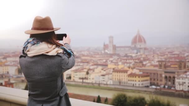 Cheerful tourist girl taking smartphone photo at amazing cityscape panorama of autumn Florence, Italy, walking away.
