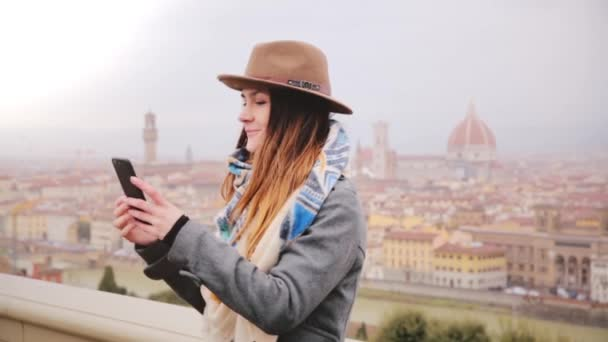 Happy smiling tourist girl taking smartphone selfie photo at amazing cityscape panorama of autumn foggy Florence, Italy.