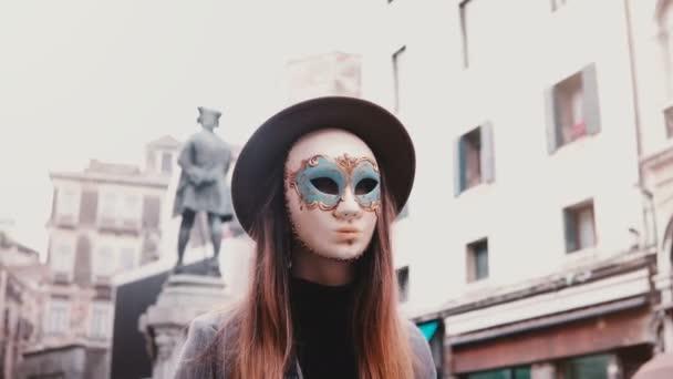 b1c26c8c704 Žena s dlouhými vlasy a klobouk nosí masku na obličej bílý karneval v  Benátkách street