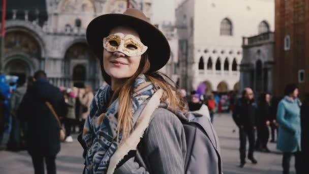 Porträt einer glücklichen Frau mit langen Haaren, die eine weiße Karnevalsmaske auf dem venezianischen Stadtplatz trägt, Italien bläst Küsse.