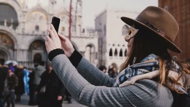 Happy woman wearing a stylish hat and white carnival face mask takes selfie photo smiling at Venice city square, Italy. Cheerful excited female traveler excited, enjoying wonderful vacation trip.