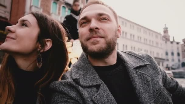Close-up shot of happy smiling young European romantic couple in gondola enjoying Venice canal tour excursion in Italy.