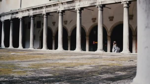 Happy tourist woman walking inside beautiful ancient building terrace with antique pillars in Venice, Italy on vacation.