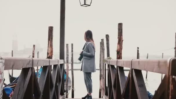 Filmszerű széles lövés boldog szép nő élvezi a tökéletes utazási pillanatok a romantikus velencei gondola pier kamerával