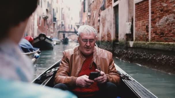 Happy senior European male traveler in gondola excited, enjoying Venice canal tour excursion on Europe retirement trip.
