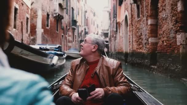 Izgatott vezető európai férfi utas gondola, mosolyogva, nézett körül a gyönyörű Velence canal tour kirándulás kirándulás.