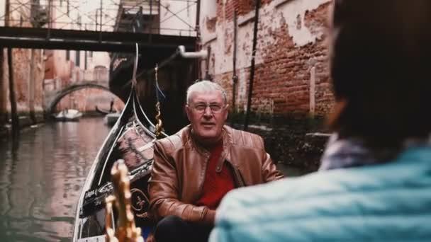 Happy smiling senior European man and woman in gondola enjoying Venice canal tour excursion on retirement trip to Italy.