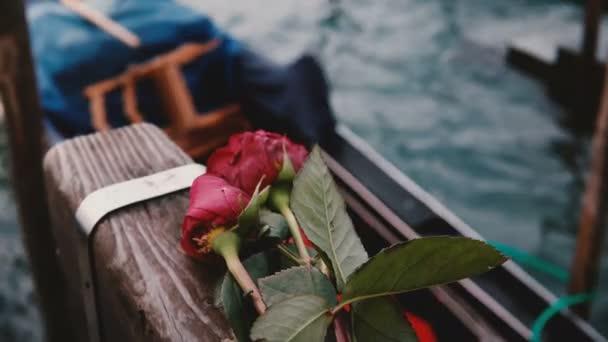 Detailní záběr krásné červené růže ležící na dřevěným kanálem molu, tradiční italská gondola houpe na vlnách v okolí.