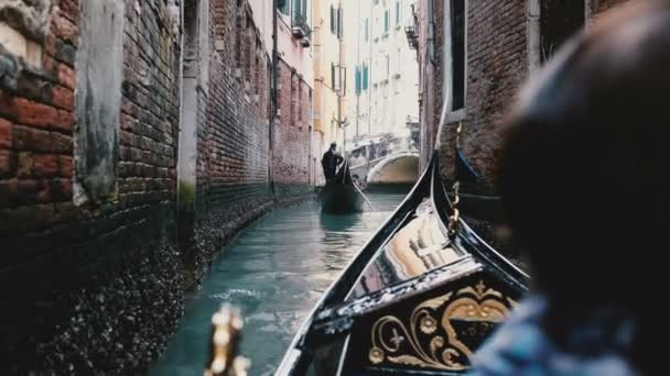 Back view of senior woman enjoying beautiful gondola excursion tour on narrow Venice canal during retirement vacation.