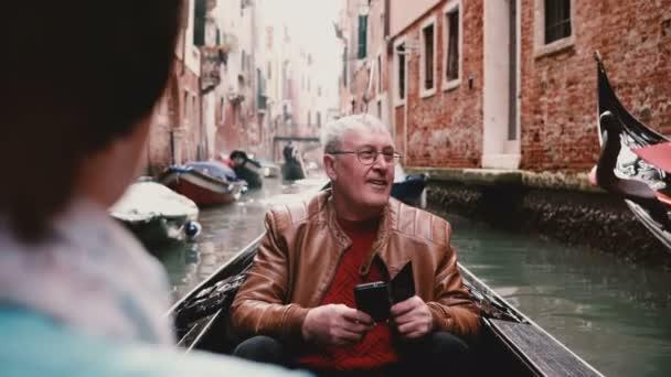 Happy senior Caucasian tourist man in gondola enjoying beautiful excursion tour on Venice canal in Italy taking photos.