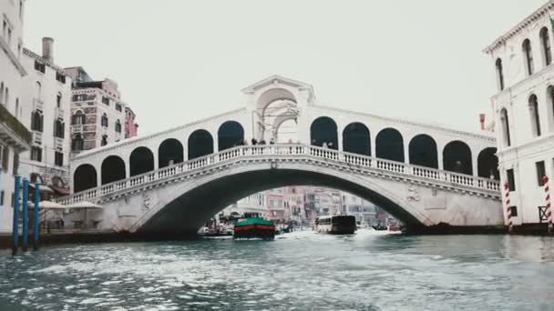 Ships passing under amazing Rialto Bridge, one of symbols of Venice, Italy and ancient heritage of world architecture.